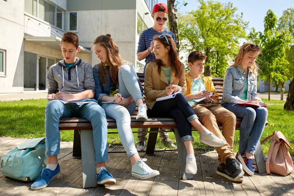 Jóvenes sentados en un banco del instituto